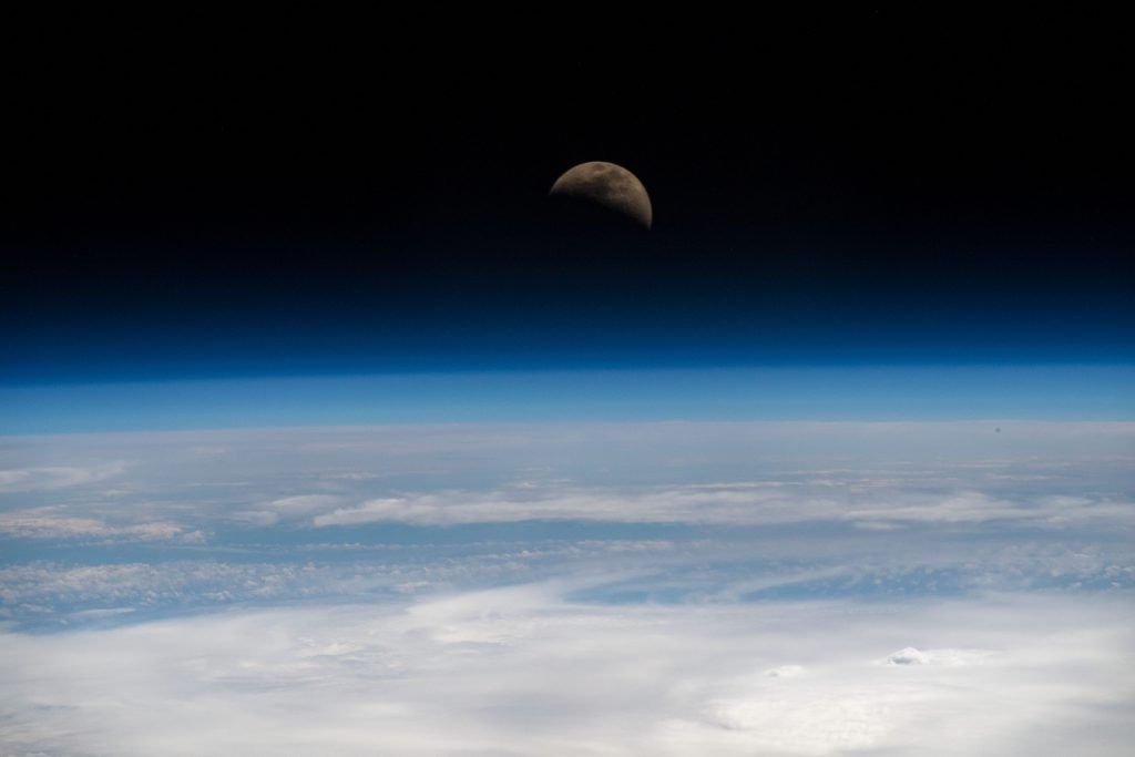First quarter moon over Earth's limb; photo taken from ISS.